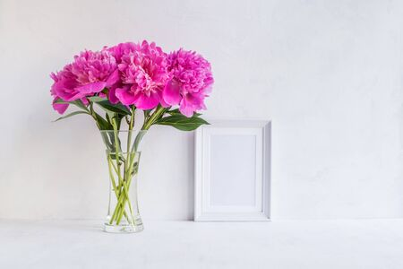Mockup with a white frame and pink peonies in a vase on a light background