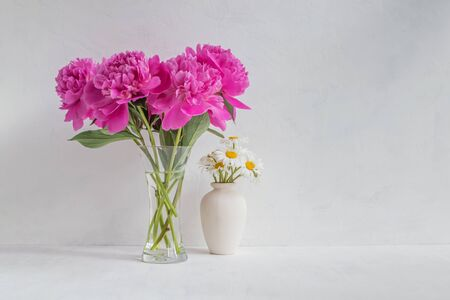 Pink peonies in a vase on a light background. Interior decor