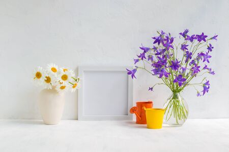 Mockup with a white frame and summer flowers in a vase on a light background