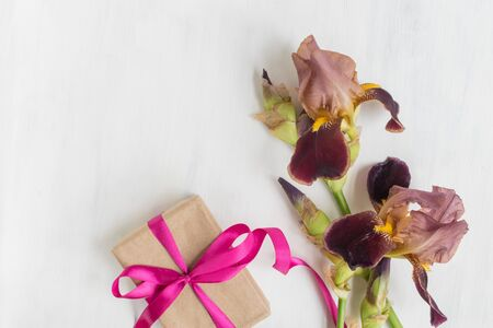 Gift box with iris flower on white background