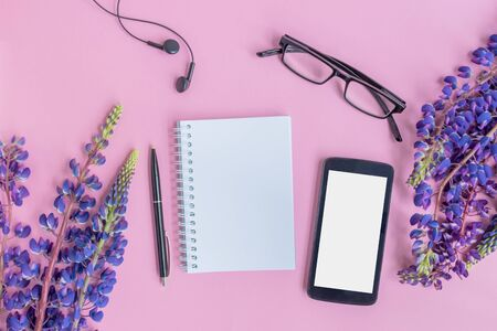 Mockup notebook with lupine flower, smartphone on a pink background empty space for your text, top view 写真素材