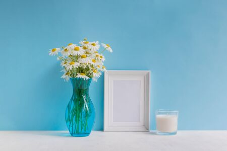 Mockup with a white frame and white daisies in a vase on a blue background