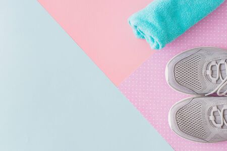 Concept of healthy lifestyle. Flat lay sport shoes, new sneakers on pastel colored background