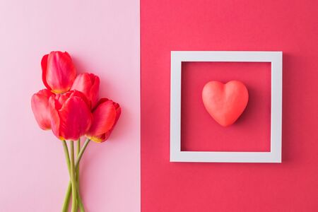 Valentines day composition with red tulips and white frame on a colored background. Flat lay, top view Stock Photo - 137497094
