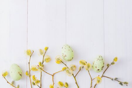 Flat lay easter composition with a willow branch and eggs on a white wooden background