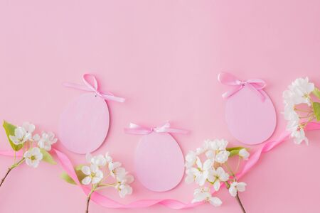 Flat lay easter composition with white spring flowers and eggs on a pink background