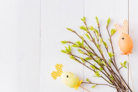 Flat lay easter composition with green buds on branches and eggs on a white wooden background