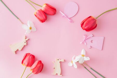 Flat lay easter composition with red tulips and eggs on a pink background