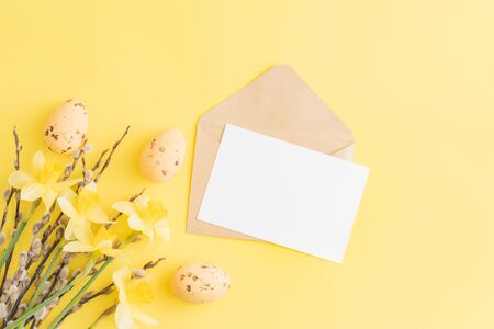 Mockup white greeting card, easter eggs and envelope with yellow daffodils on a yellow background