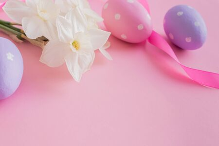Easter composition with white daffodils and eggs on a pink background