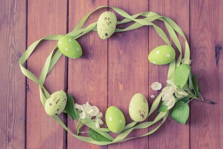 Flat lay wreath with easter eggs and white spring flowers on a wooden background