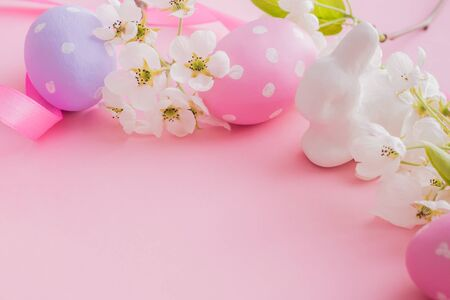 Easter composition with white spring flowers and eggs on a pink background
