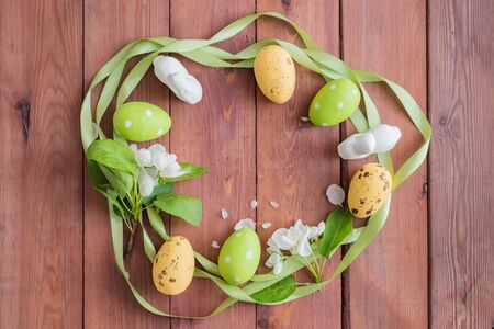 Flat lay composition with white spring flowers and easter eggs on a wooden background