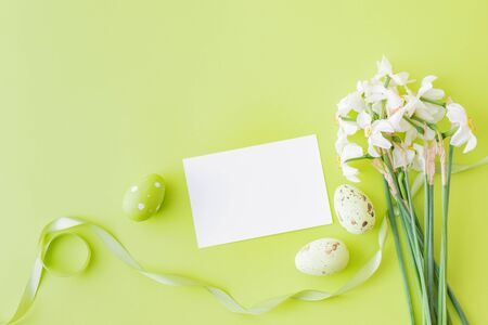 Mockup white greeting card and easter eggs with white daffodils on a green background