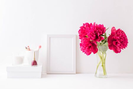 Home interior with decor elements. White frame, red peonies in a vase, cosmetic set