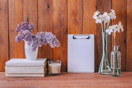 Home interior with decor elements. Mockup clipboard, white daffodils in a vase, interior decoration 免版税图像