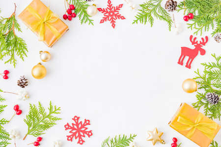 Flat lay frame with evergreen tree branch, christmas decorations and gift box on a white background