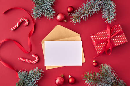 Mockup white greeting card and envelope with red christmas balls, spruce branches and gift box on a red background