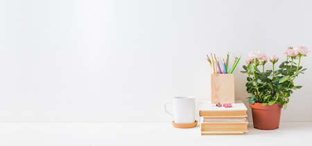 Home office, interior for bloggers workplace with roses in a pot, books, white mug, office supplies