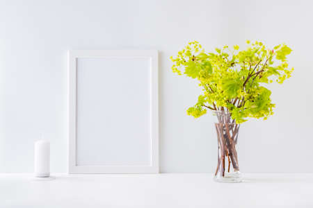 Mockup with a white frame and branches with green leaves in a vase on a white table