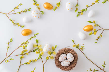 Flat lay easter composition with a willow branch and eggs on a white background