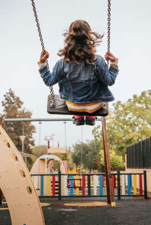 girl swinging on a swing in a public park Banque d'images