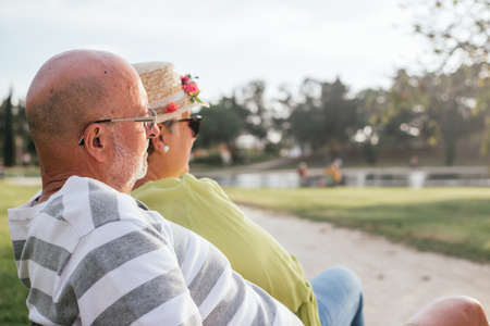 pensioners couple close-up sitting on a park