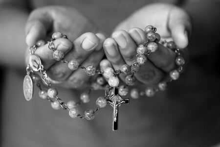 Rosary in hand in black and white. Young junior lady holding rosary with open hand with Jesus Christ Cross Crucifix. Month of Rosary, Christian Catholic religious symbol of faith concept. Imagens