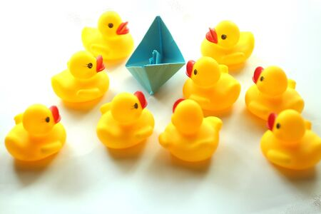 A blue boat paper and cute yellow rubber ducks. Togetherness, and teamwork concept in white background Stock fotó