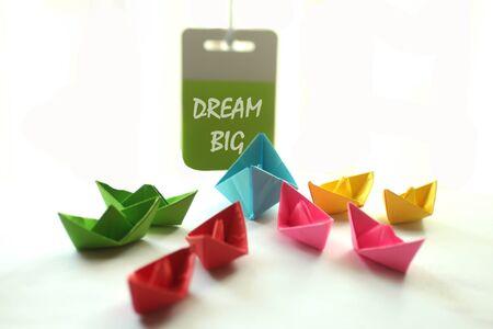 Citation de motivation - Dream Big. Avec des bateaux en papier colorés et une note de motivation accrochée au mur pour l'équipe. Concept de travail d'équipe, de leadership et de convivialité sur fond blanc.