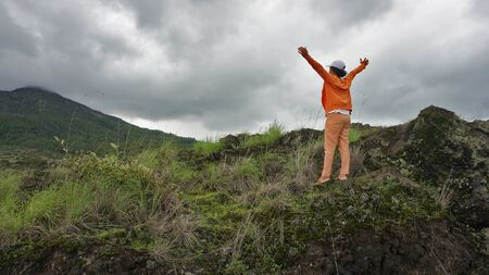 Young woman standing hand raised with open arms against mountain scenery & blue gloomy sky. Showing freedom and healing concept.