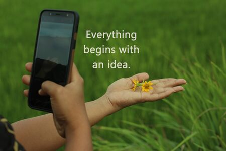 Inspirational motivational quote - Everything begins with an idea, with smartphone photographer capturing flowers in her hand, creating concept. Smartphone photographer capturing creative angel. One hand holds daisy little flowers, the other hands taking picture concept.