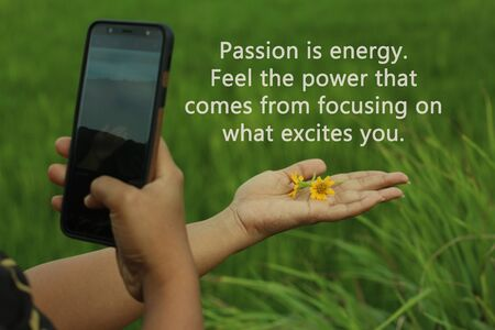 Inspirational motivational quote - Passion is energy. Feel the power that comes from focusing on what excites you, with smartphone photographer capturing flowers in her hand, creating concept. Smartphone photographer capturing creative angel. One hand holds daisy little flowers, the other hands taking picture concept. Banco de Imagens