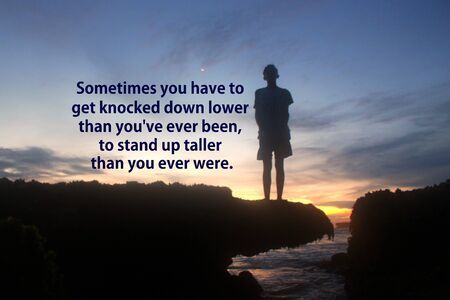 Inspirational motivational quote - Sometimes you have to get knocked down lower than you have ever been, to stand up taller that you ever were. With young boy silhouette stands alone on sea rock. Dramatic gloomy moody sunset sky and beach backgrounds. Stock Photo