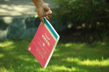 Hand holding a sign. Book belong to mama. Mothers day concept. Stock Photo