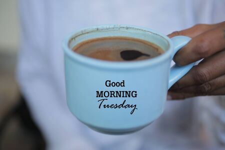 Cup of coffee in hand. Good morning Tuesday greeting on cup of coffee. Morning coffee concept. 免版税图像