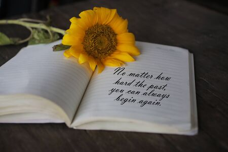 Inspirational quote - No matter how hard the past you can always begin again. With notes on a book and sun flower blossom on rustic table background. Imagens