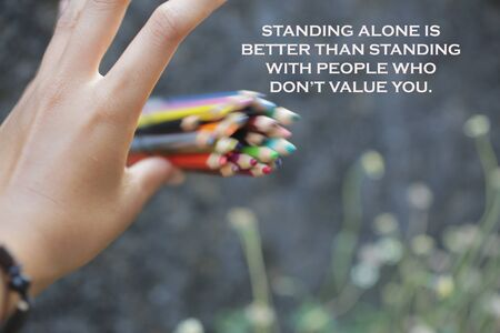 Inspirational quote - Standing alone is bettern than standing with people who do not value you. With an illustration background of young woman hand release a bunch of colored pencils in the air.