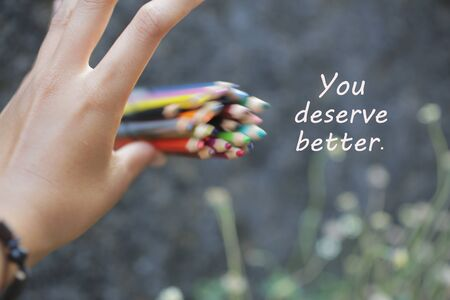 Inspirational quote - You deserve better. With an illustration background of young woman hand release a bunch of colored pencils in the air. 版權商用圖片