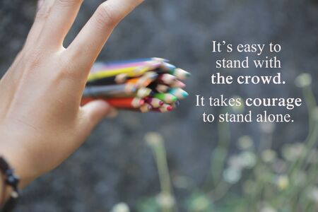 Inspirational quote - It is easy to stand with the crowd. I takes courage to stand alone. With an illustration background of young woman hand release a bunch of colored pencils in the air.