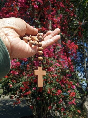 Senior woman holding wooden  rosary in hand with Jesus Christ Cross Crucifix. Christian Catholic religious symbol of faith concept. With nature background of bougainvillea flowers & the trees.