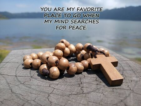 Inspirational quote - You are my favorite place to go when my mind searches for peace. With blue lake background & wooden rosary on wood with Jesus Christ Cross Crucifix. Christian Catholic religious symbol of faith concept.