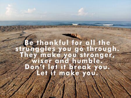 Inspirierendes Zitat - Seien Sie dankbar für all die Kämpfe, die Sie durchmachen. Sie machen dich stärker, weiser und bescheidener. Lass dich nicht davon brechen. Lassen Sie es Sie machen, mit rustikalem Holztischhintergrund und blauem Himmel und Meer.