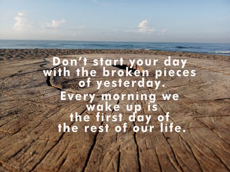 Inspirational quote - Do not start your day with the broken pieces of yesterday. Every morning we wake up is the first day of the rest of our life.With wooden rustic table texture background and blue sky in the beach. Stock Photo