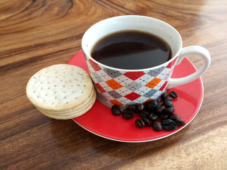A cup of black morning coffee with cookies, raw coffee beans on wooden table. Fresh morning coffee drink concept. Copy space.
