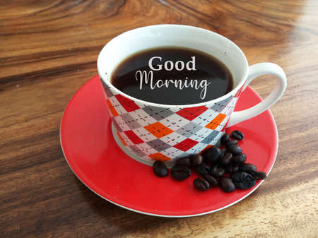 Morning coffee. A cup of black coffee and raw coffee beans with  text greeting - Good morning. On natural background of wooden table. Fresh morning with coffee drink concept.