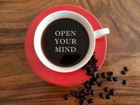 Inspirational motivational quote - open your mind. On background of a cup of hot black coffee and roasted coffee beans decoration on wooden table. Fresh morning coffee drink concept with words.