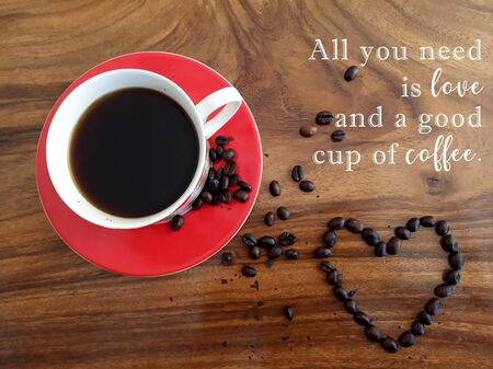 Inspirational motivational quote - All you need is love and a good cup of coffee. With background of hot black coffee and raw coffee beans love shape on wooden table. Morning coffee & love concept.
