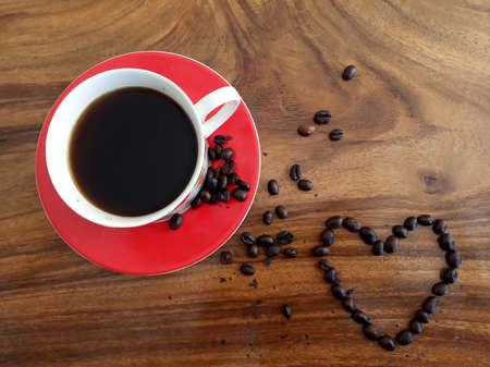 A cups of hot black coffee and love sign of roasted coffee beans decoration. On background of wooden table in high angle view, or top view. Food or drink flat lay concept. Copy space.