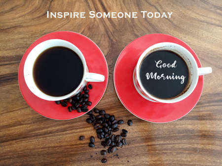 Morning coffee with inspirational quote and greeting - Inspire someone today. Good morning. On background of two cups of black coffee & raw coffee beans on wooden table. Top view or high angle view.
